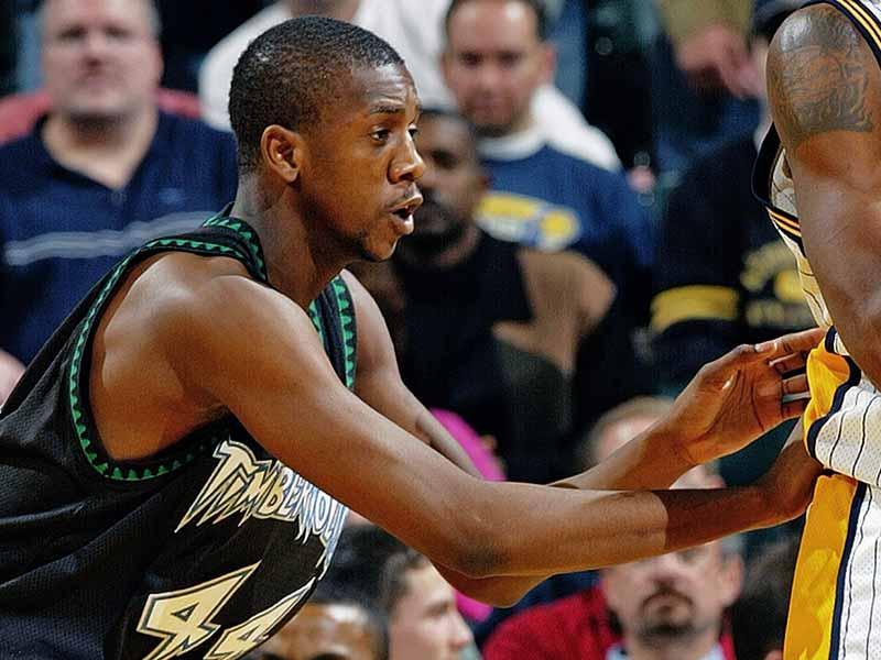 Ndudi Ebi of Timberwolves peaking towards his teammates behind his opponent